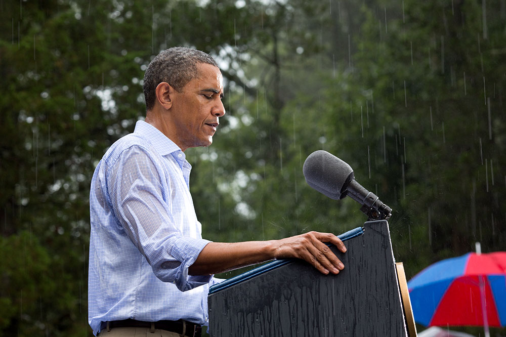 """July 14, 2012 """"The President delivers remarks in the pouring rain at a campaign event in Glen Allen, Va. He was supposed to do a series of press interviews inside before his speech, but since people had been waiting for hours in the rain he did his remarks as soon as he arrived onsite so people."""" (Official White House Photo by Pete Souza) This official White House photograph is being made available only for publication by news organizations and/or for personal use printing by the subject(s) of the photograph. The photograph may not be manipulated in any way and may not be used in commercial or political materials, advertisements, emails, products, promotions that in any way suggests approval or endorsement of the President, the First Family, or the White House.Ê"""
